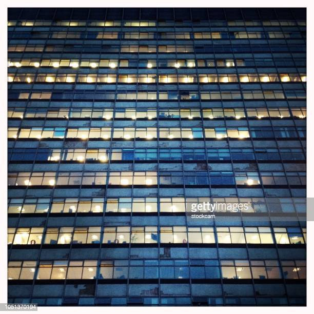 facade of office building at dusk - großunternehmen stock pictures, royalty-free photos & images