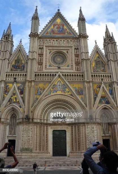 Facade of Orvieto Cathedral with tourist photographing