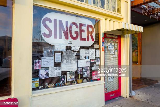 Facade of Singer sewing machine dealership on Solano Avenue in Berkeley California with eclectic signage in shop window including sign claiming to be...