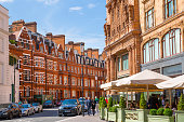Facade of the Harrods store and little street cafe in Kensington, the one of the most expensive shopping places in Europe