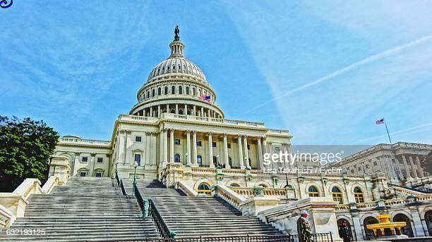 facade of united states capitol against sky - politics and government stock pictures, royalty-free photos & images