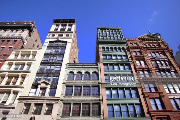 facades of cast-iron historical buildings along broadway in soho, manhattan, new york city - soho manhattan - fotografias e filmes do acervo
