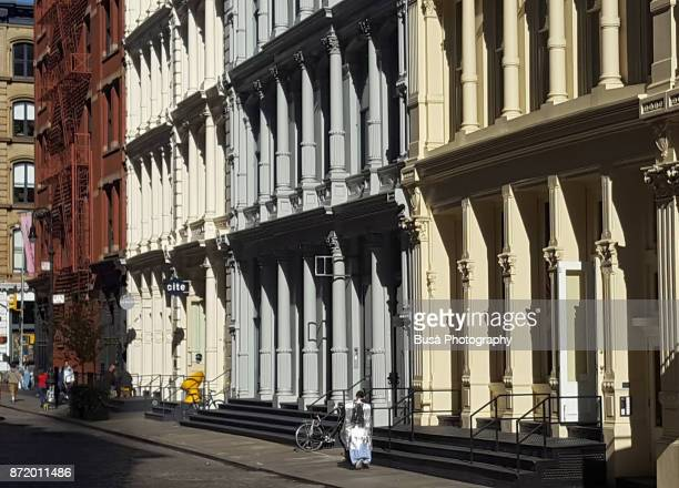 facades of typical cast iron buildings with fire escapes along greene street in the soho cast iron historic district, manhattan, new york city - ニューヨーク ソーホー ストックフォトと画像