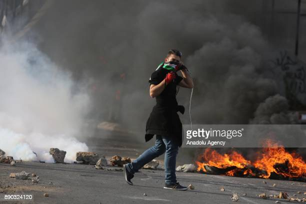 A face covered Palestinian protester prepares to throw a rock with a slingshot in response to Israeli security forces' intervention in a...