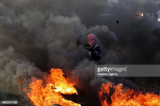 A face covered Palestinian protester throws a rock with a slingshot in response to Israeli security forces' intervention in a demonstration against...