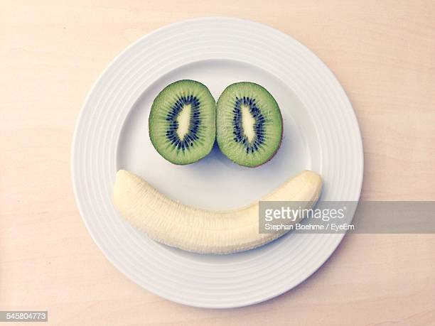 face made from banana and kiwi on plate - smiley face stock pictures, royalty-free photos & images