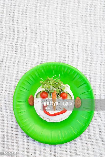 Face made from fresh food on green plate