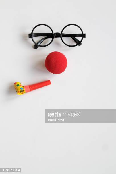face made with glasses, red nose and party horn blower - clown stock-fotos und bilder