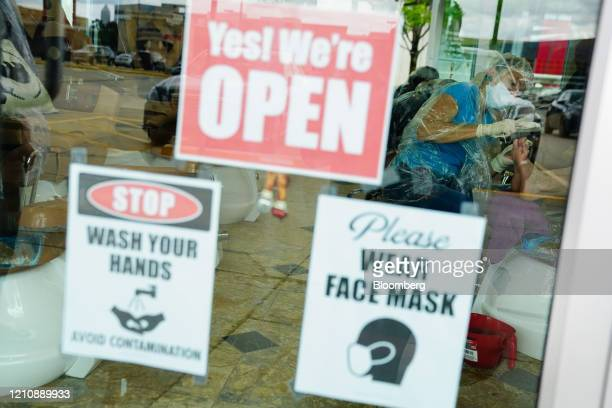 Face mask and hand washing signs are displayed on the door of a nail salon in Atlanta Georgia US on Friday April 24 2020 Georgia's hair salons tattoo...