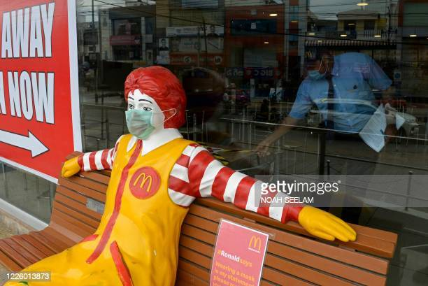 Face mask is seen on Ronald McDonald, the mascot of fast-food company McDonald's, as an employee works inside its outlet after the authorities eased...