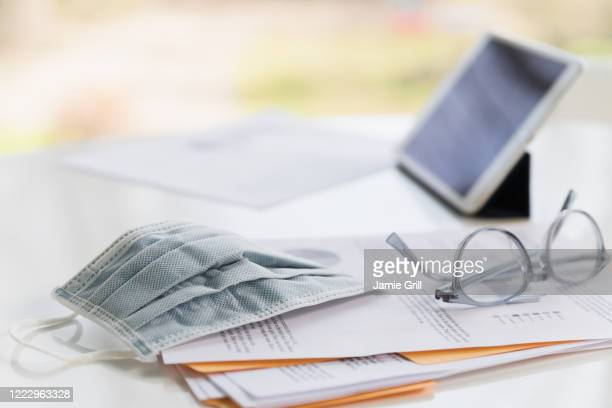face mask on business papers and tablet - montclair stockfoto's en -beelden
