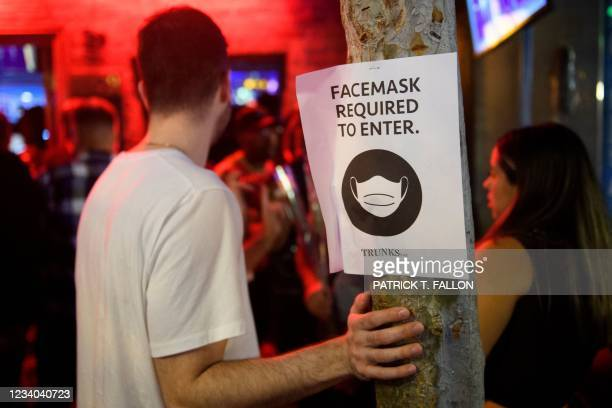 Face mask signage is displayed outside the Trunks bar after midnight early Sunday morning on July 18, 2021 in West Hollywood, California. - Wearing a...