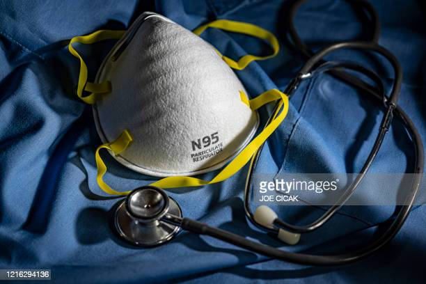n95 face mask with stethoscope and scrubs - n95 face mask stock pictures, royalty-free photos & images
