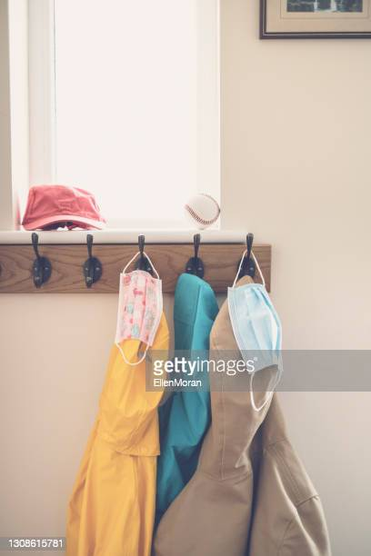 face masks on coat hooks - coat stock pictures, royalty-free photos & images