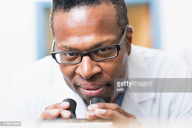 Face of a black man in lab coat using microscope