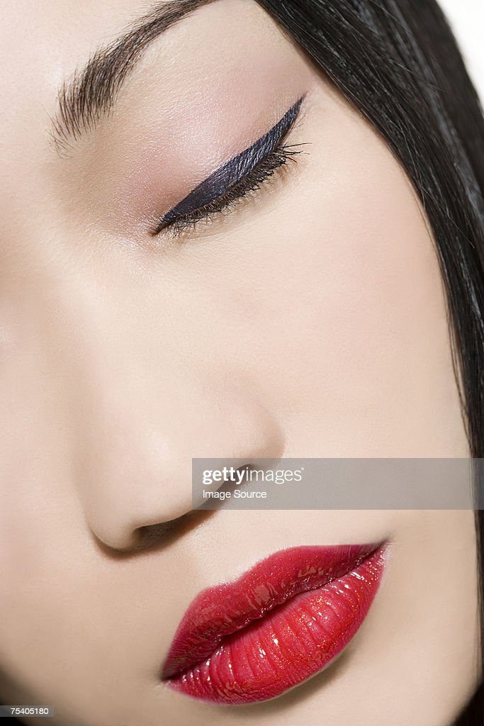 Face of a woman with eyeliner and lipstick : Stock Photo