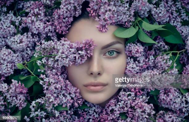 Face of Caucasian woman surrounded by purple flowers