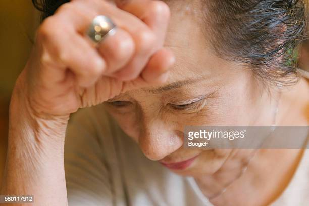 Face of Mature Japanese Woman Feeling Migraine Headache Pain