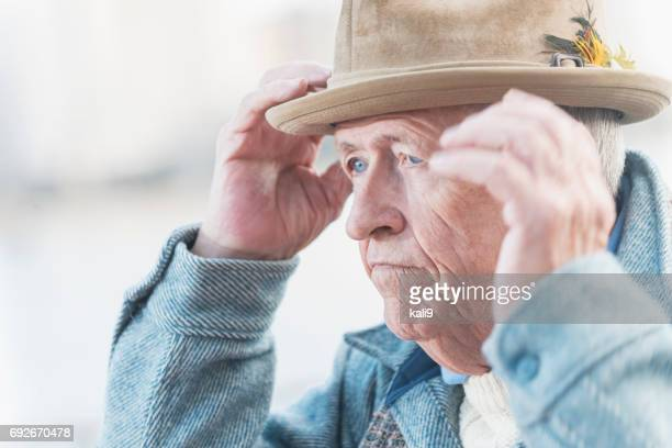Face of old man with serious expression putting on hat