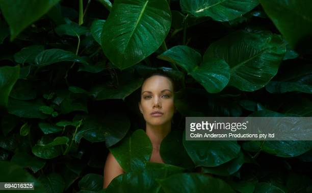 Face of Pacific Islander woman surrounded by wet leaves