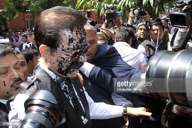 Face of Sahara Chairman Subrata Roy covered with ink thrown by an assailant as he arrives at the Supreme Court on March 4 2014 in New Delhi India...