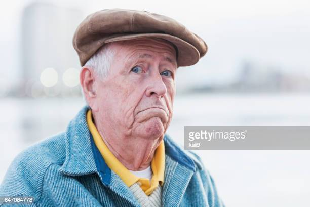 face of senior man wearing flat cap, frowning - flat cap stock pictures, royalty-free photos & images