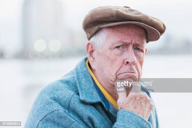 Face of senior man wearing flat cap, frowning