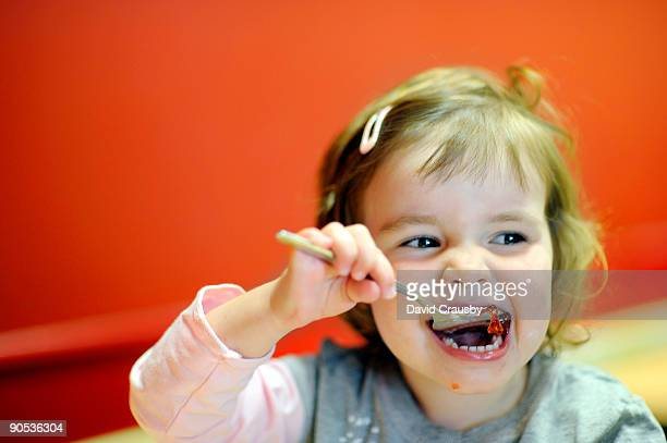 face of toddler eating jelly from a spoon - crausby stock pictures, royalty-free photos & images