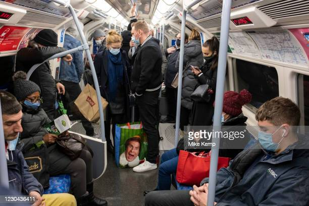 Face of Will Ferrell on an Elf shopping bag amongst commuters on a busy underground train on 4th December 2020 in London, United Kingdom. Elf is a...
