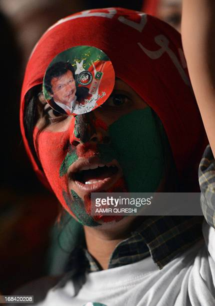 Face painted supporter of Pakistani politician and former cricketer Imran Khan takes part during the last election campaign meeting in Islamabad on...
