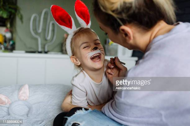 face painting for smiling easter bunny - happy easter mom stock pictures, royalty-free photos & images