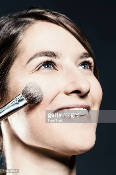 Face powder being applied to young womans cheek