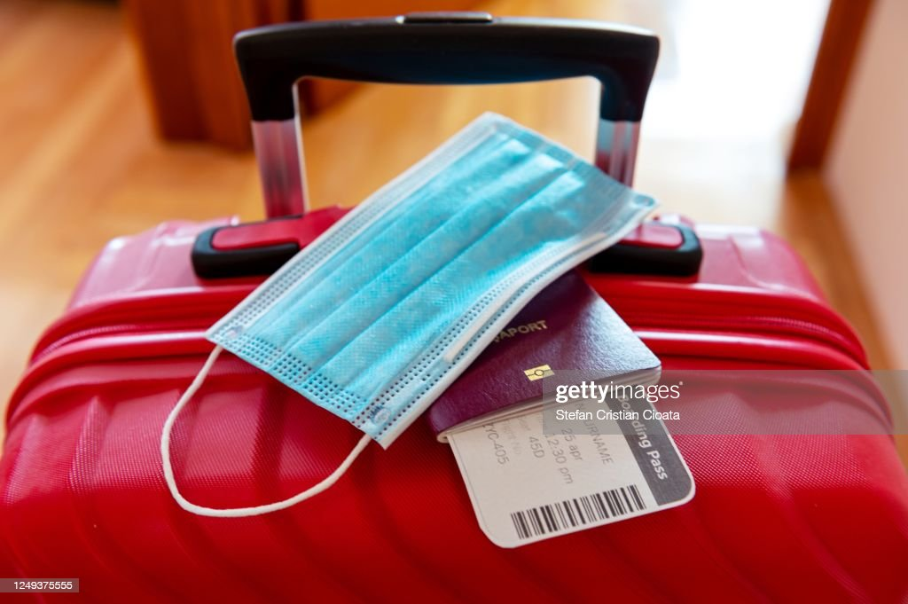 Face protection mask over passport and boarding ticket : Stockfoto
