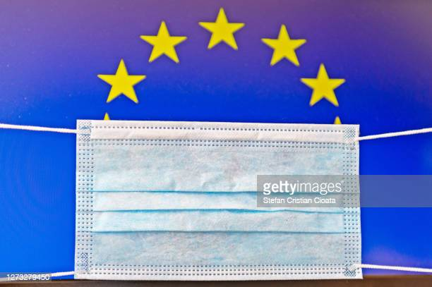 face protective mask and european union flag - disease vector stock pictures, royalty-free photos & images