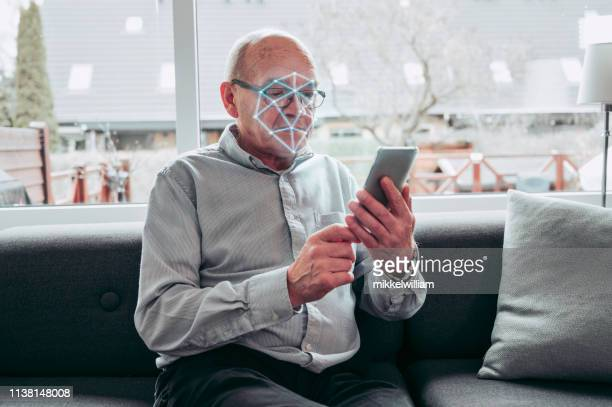 face recognition software on smart phone performs facial scan of senior man - sensor stock pictures, royalty-free photos & images