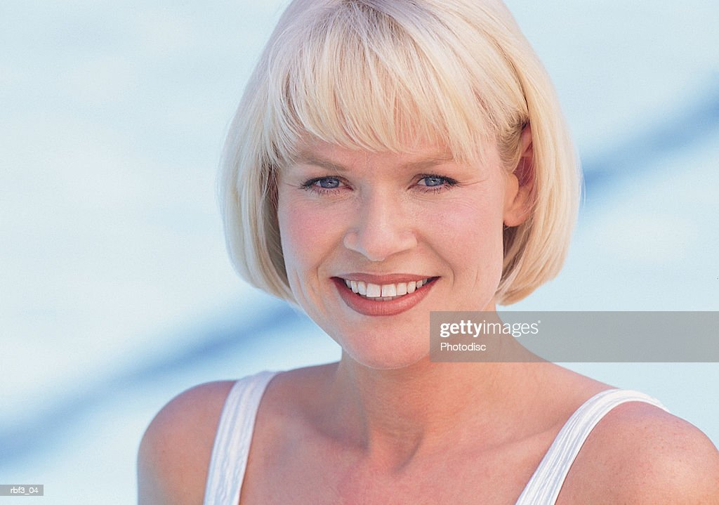 face shot of a blonde college-aged woman wearing a white bikini as she smiles : Stockfoto