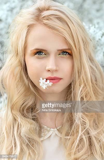 Face shot of blonde girl with blossom in her lips