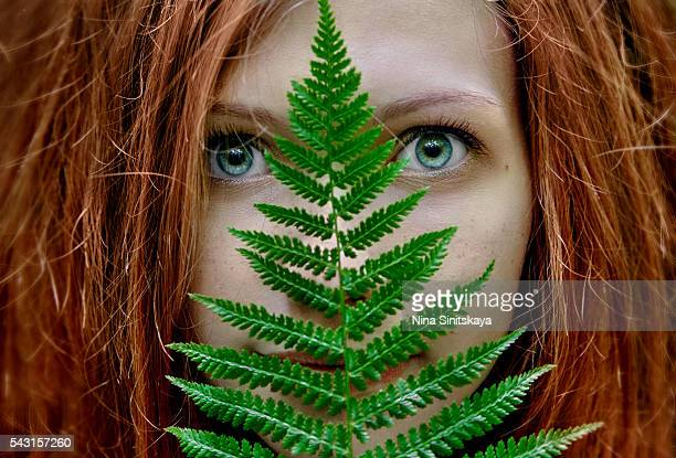 face shot of red young woman with green eyes hiding face behind the fern - green eyes stock pictures, royalty-free photos & images