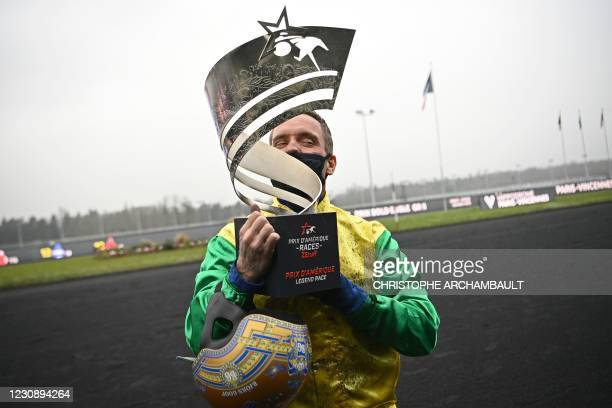 Face Time Bourbon' Swedish driver Bjorn Goop poses with the trophy after winning the Prix d'Amerique race, commonly known as the World Driven Trot...