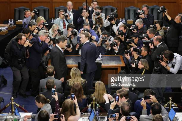 Facebook cofounder Chairman and CEO Mark Zuckerberg speaks with a colleague as he arrives to testify before a combined Senate Judiciary and Commerce...
