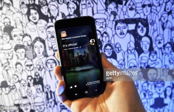 A Facebook employee displays an HTC phone with the new Home operating system against the backdrop of a decorated wall at Facebook's Headquarters...