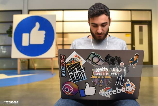 Facebook employee Mohamed Almari works from his laptop decorated in various Facebook stickers at the company's corporate headquarters campus in Menlo...