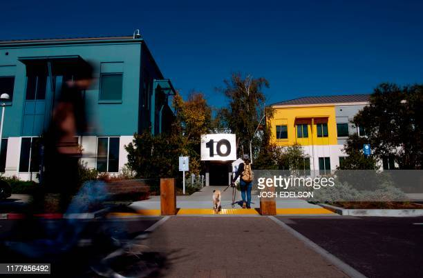Facebook employee rides a bike past building 10 at Facebook's corporate headquarters campus in Menlo Park, California, on October 23, 2019.