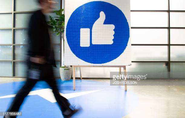"Facebook employee walks by a sign displaying the ""like"" sign at Facebook's corporate headquarters campus in Menlo Park, California, on October 23,..."