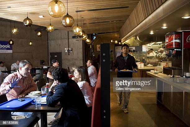 Facebook employees gather for lunch at one of the company's several free restaurants which employ thirty five cooks and offer themed foods from...