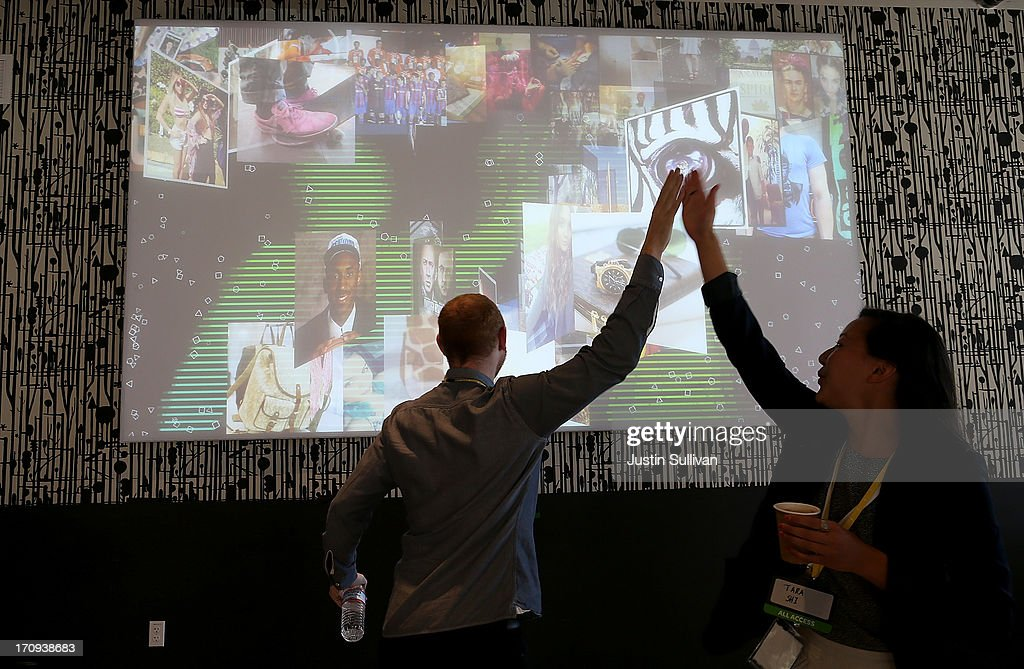 Facebook employees high five in front of a Instagram video display during a press event at Facebook headquarters on June 20, 2013 in Menlo Park, California. Facebook announced that its photo-sharing subsidiary Instagram will now allow users to take and share video.