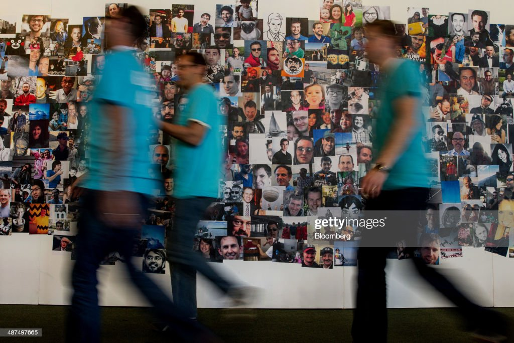 Facebook Inc. employees walk past a wall of images during the company's F8 Developers Conference to begin in San Francisco, California, U.S., on Wednesday, April 30, 2014. Facebook Inc. will offer software developers improved tools to create programs that run on any smartphone and a more streamlined experience for people to log into apps, including the option to sign in anonymously. Photographer: Erin Lubin/Bloomberg via Getty Images