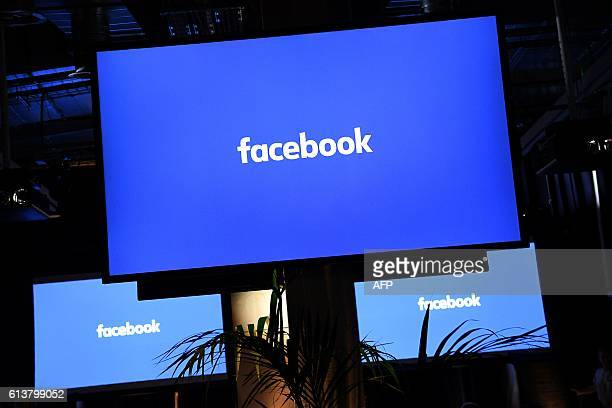 A Facebook logo is pictured on a screen ahead of a press conference to announce the launch of it's latest product 'Workplace' in central London on...
