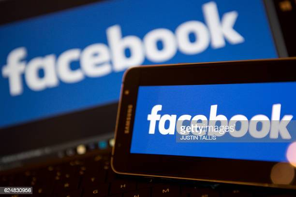 Facebook logos are pictured on the screens of a smartphone and a laptop computer in central London on November 21 2016 Facebook on Monday became the...