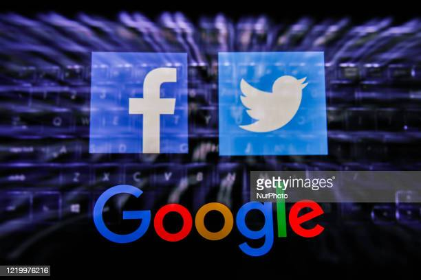 Facebook, Twitter and Google logos displayed on a phone screen and keyboard are seen in this multiple exposure illustration photo taken in Poland on...